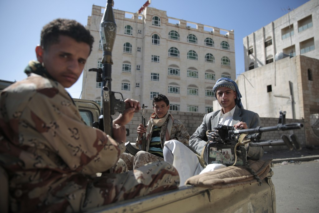 FILE - This Apr. 19, 2017 file photo, Shiite fighters, known as Houthis, pose for a photo as they secure a road, as people take part in a march from S