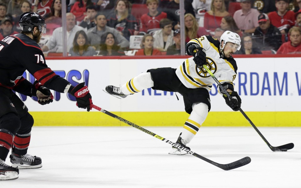 Boston Bruins' Brad Marchand (63) takes a shot on goal while Carolina Hurricanes' Jaccob Slavin (74) defends during the first period in Game 4 of the