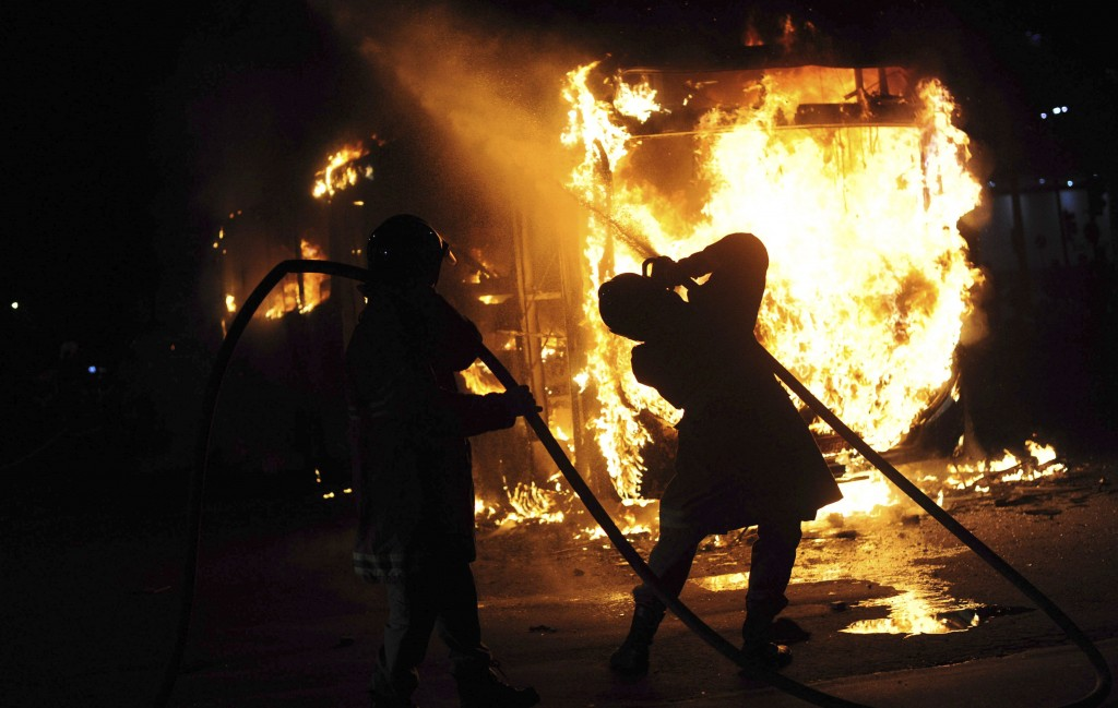 In this May 15, 2019 photo, a firefighter extinguishes a burning bus that was torched during a nation-wide education strike, in Rio de Janeiro, Brazil