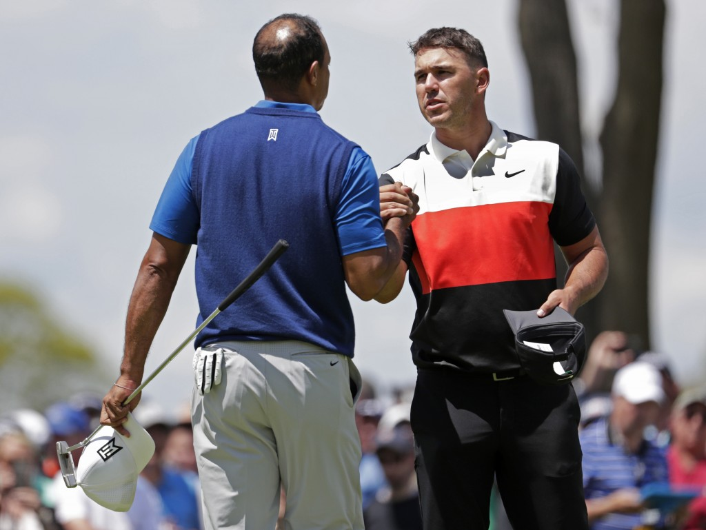 Brooks Koepka, right, shakes hands with Tiger Woods after finishing the first round of the PGA Championship golf tournament, Thursday, May 16, 2019, a