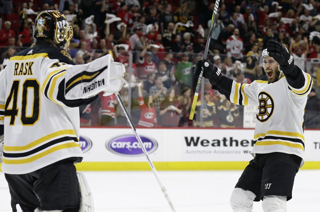 Boston Bruins goalie Tuukka Rask (40), of Finland, celebrates with John Moore following Game 4 of the NHL hockey Stanley Cup Eastern Conference finals