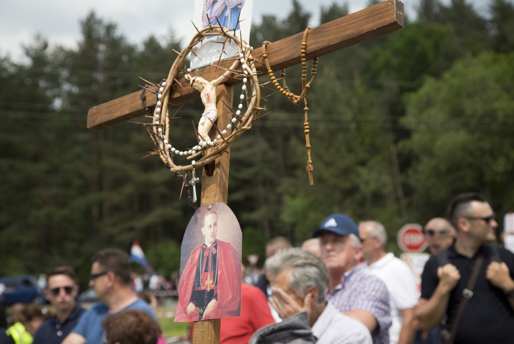 FILE - In this Saturday, May 12, 2018 file photo, a mourner holds a crucifix during a commemoration ceremony in Bleiburg, Austria. Thousands will gath...