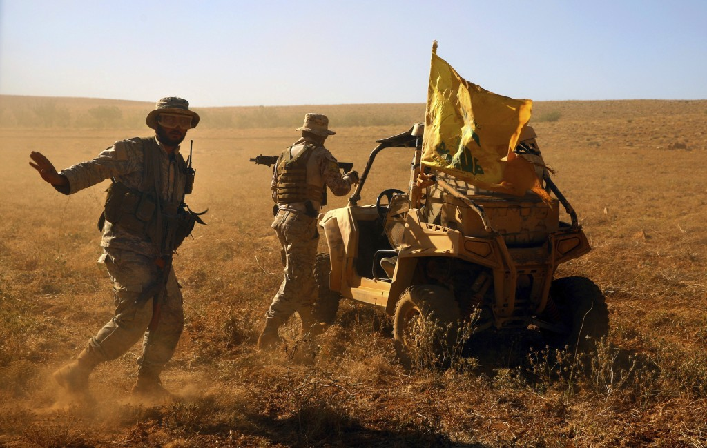 FILE - This July 29, 2017 file photo, Hezbollah fighters stand near a four-wheel vehicle positioned at the site where clashes erupted between Hezbolla...