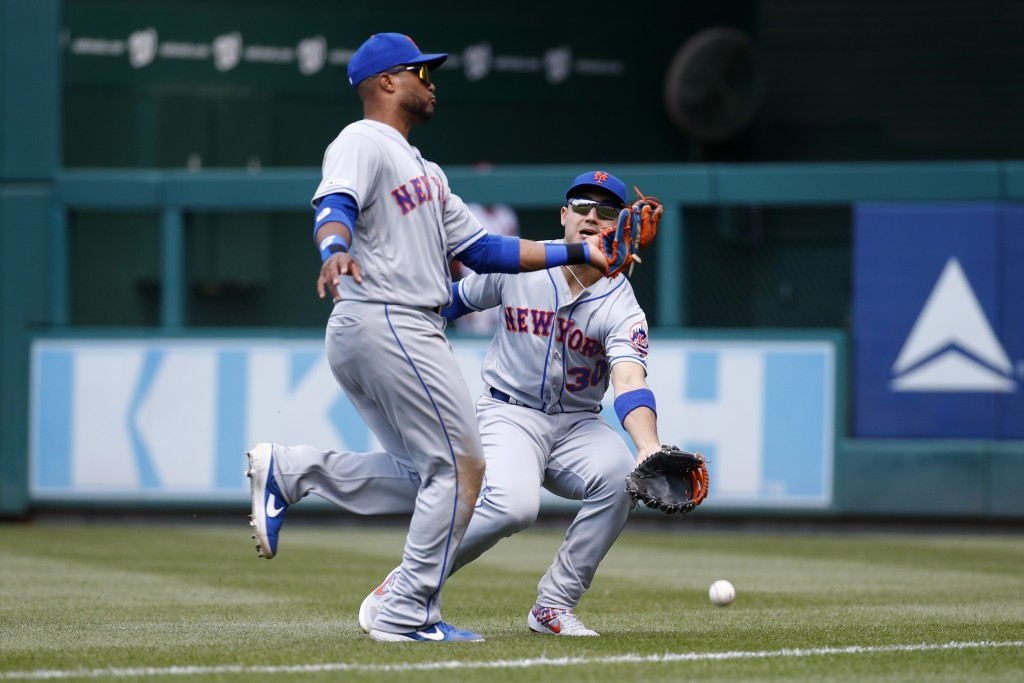 New York Mets right fielder Michael Conforto, right, collides with second baseman Robinson Cano as they fail to catch a fly ball that was hit by Washi