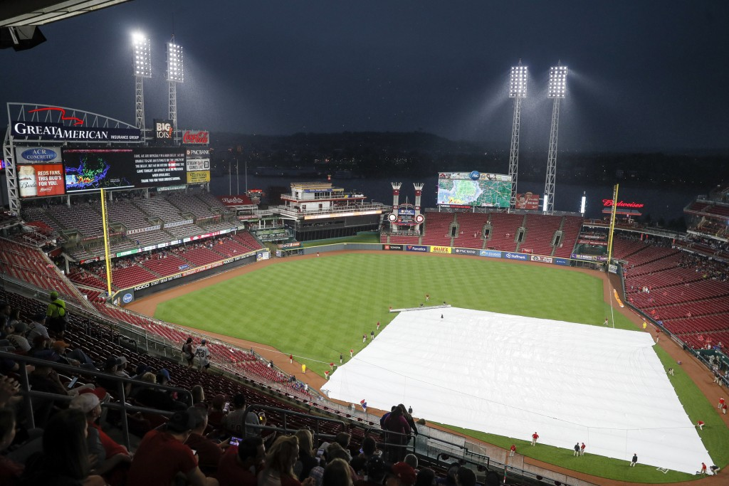 Members of the grounds crew pull a tarp over the infield during a rain delay in the sixth inning of a baseball game between the Cincinnati Reds and th