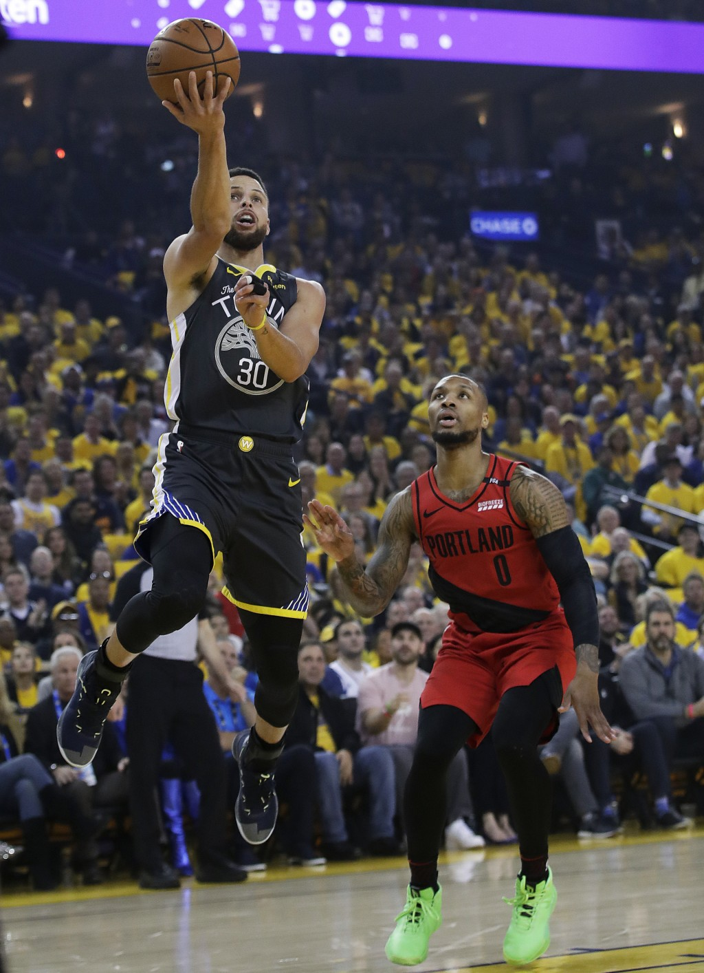 Golden State Warriors guard Stephen Curry (30) shoots next to Portland Trail Blazers guard Damian Lillard (0) during the first half of Game 2 of the N