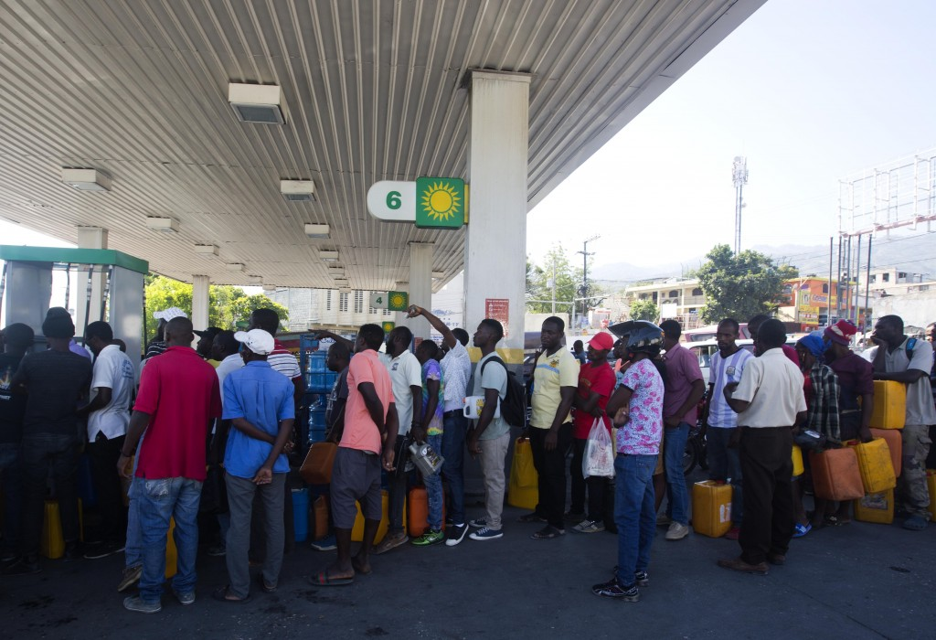 In this April 10, 2019 photo, people line up at a gas station to fill containers with fuel, in Port-au-Prince, Haiti. As Venezuelan President Nicolás ...