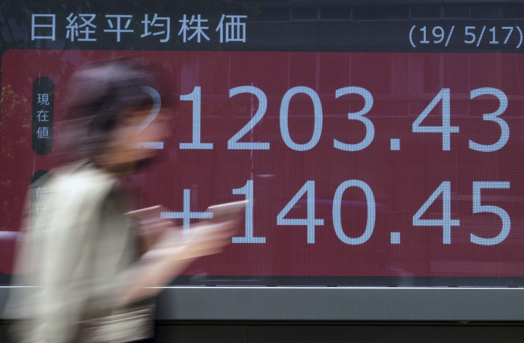 A woman walks past an electronic stock board showing Japan's Nikkei 225 index at a securities firm in Tokyo Friday, May 17, 2019. Asian stocks were mi