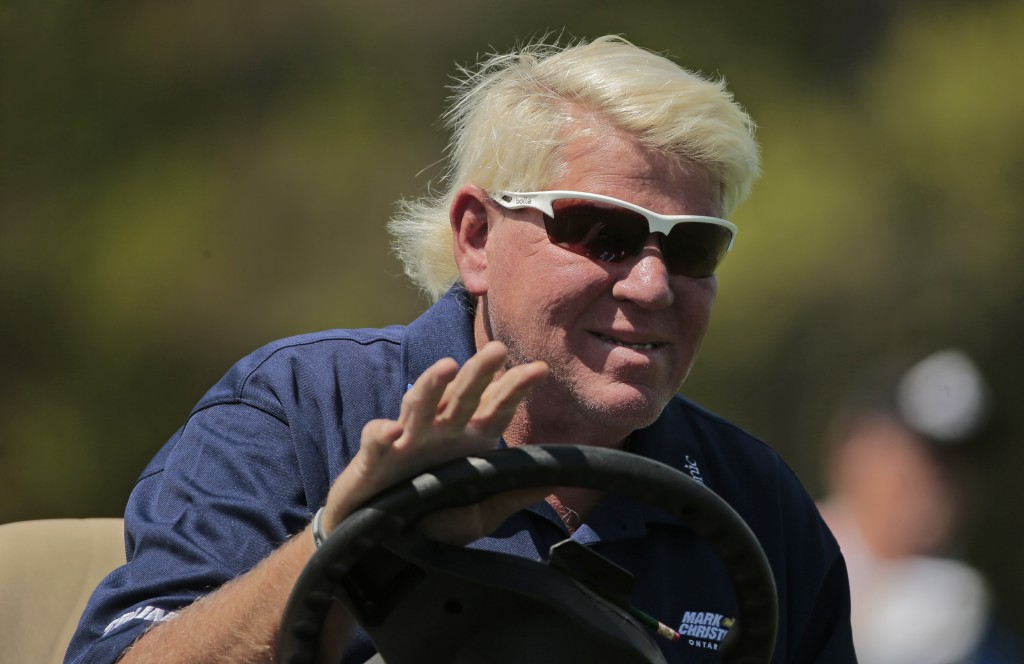 John Daly waves to golf fans as he drives down the 16th fairway during the first round of the PGA Championship golf tournament, Thursday, May 16, 2019