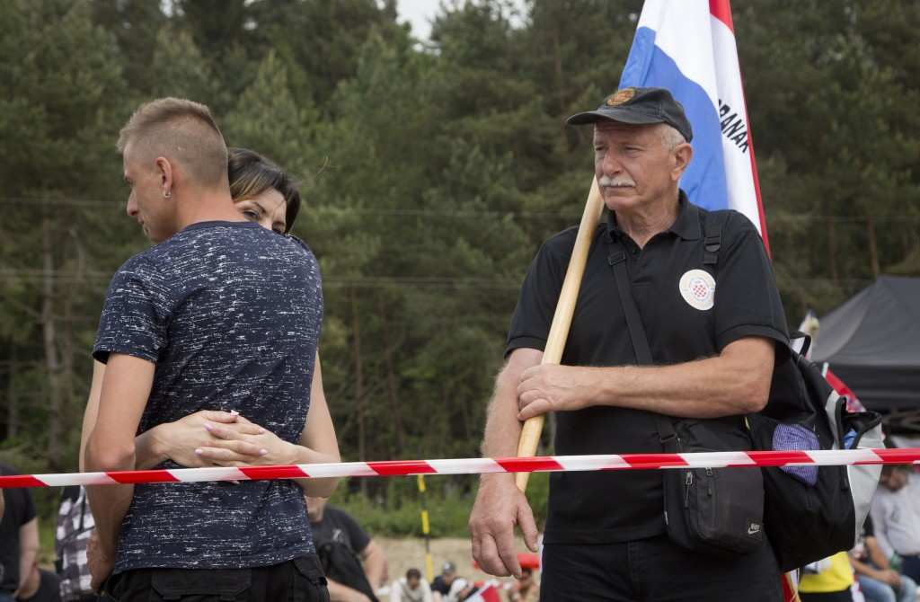 FILE - In this Saturday, May 12, 2018 file photo, a man holds Croatian flag as a couple embraces at the memorial site in Bleiburg, Austria. Thousands ...