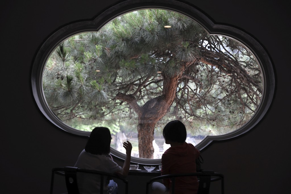 Visitors enjoy the scene from a window of the Xiangshan hotel designed by Chinese-American architect I.M. Pei and built in 1982 in Beijing, China on F...