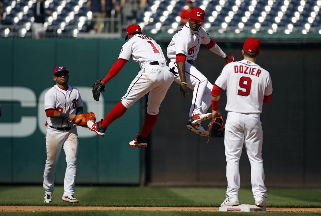 Washington Nationals shortstop Wilmer Difo (1) and center fielder Victor Robles, second from right, celebrate in front of teammates Gerardo Parra, bac