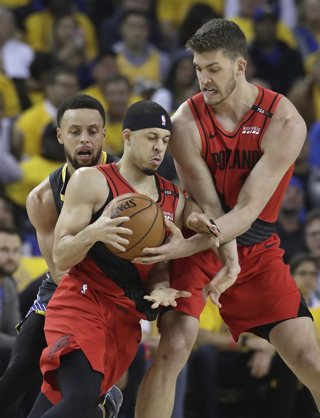 Portland Trail Blazers guard Seth Curry, center, controls the ball next to forward Meyers Leonard, right, as he is is defended by Golden State Warrior