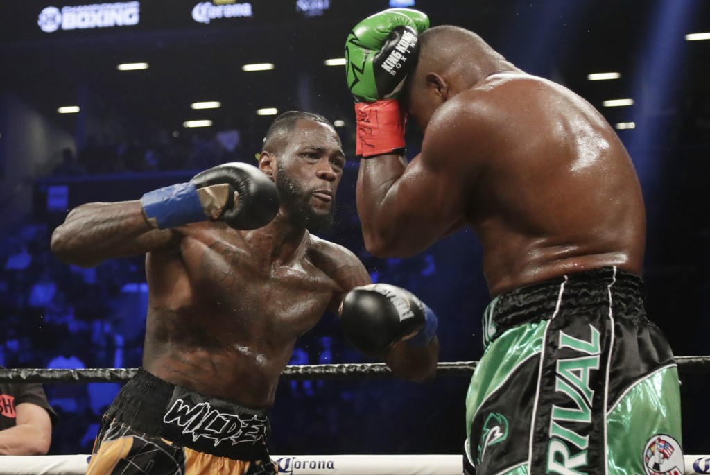 FILE - In this March 3, 2018, file photo, Deontay Wilder, left, fights Luis Ortiz during the third round of the WBC heavyweight championship bout in N