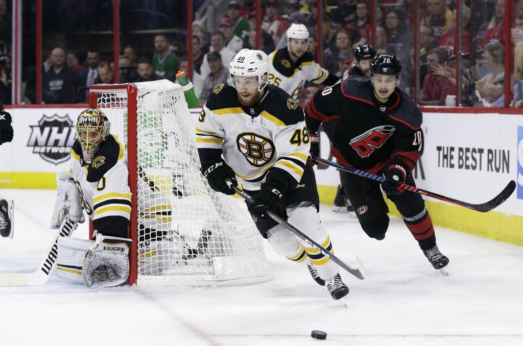 Boston Bruins' Matt Grzelcyk (48) controls the puck against a chasing Carolina Hurricanes' Sebastian Aho (20), of Finland, as Bruins goalie Tuukka Ras