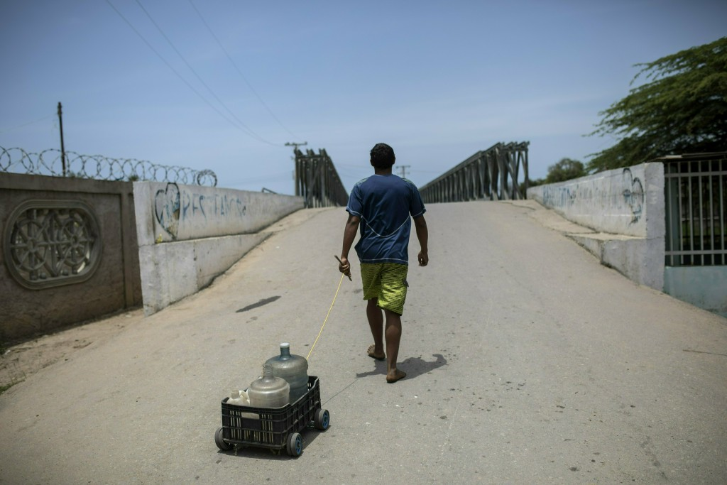 A man pulls a crate on wheels with empty bottles as he fetches potable water in Machurucuto, Venezuela, Sunday, May 5, 2019. Fifty-two years ago this