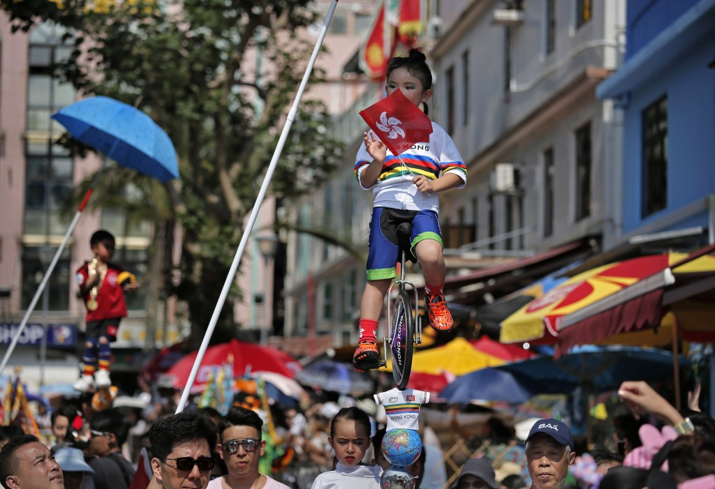 In this Sunday, May 12, 2019, file photo, a child dressed in a traditional Chinese costume floats in the air, supported by a rig of hidden metal rods,