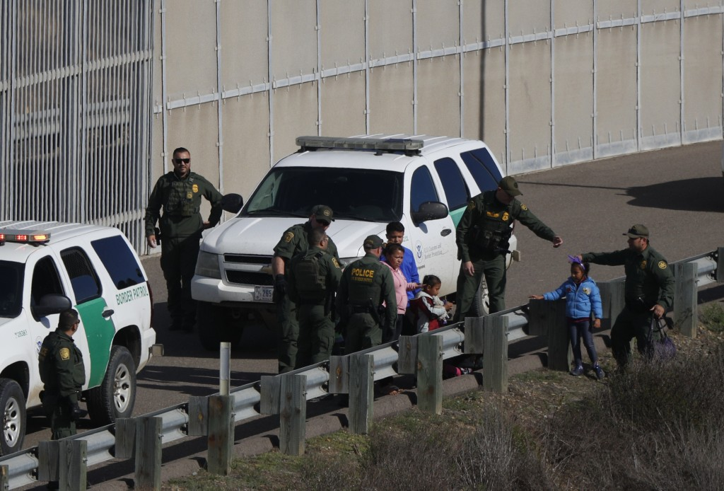 FILE - In this Dec. 9, 2018 file photo, a woman and children are ushered into cars by U.S. Border Patrol agents after crossing illegally over the bord