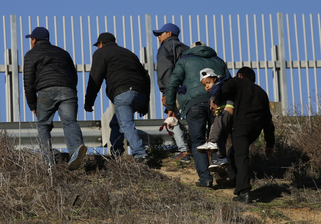 FILE - In this Dec. 12, 2018 file photo, Honduran migrants, one carrying a child, who plan to turn themselves over to U.S. border patrol agents, walk