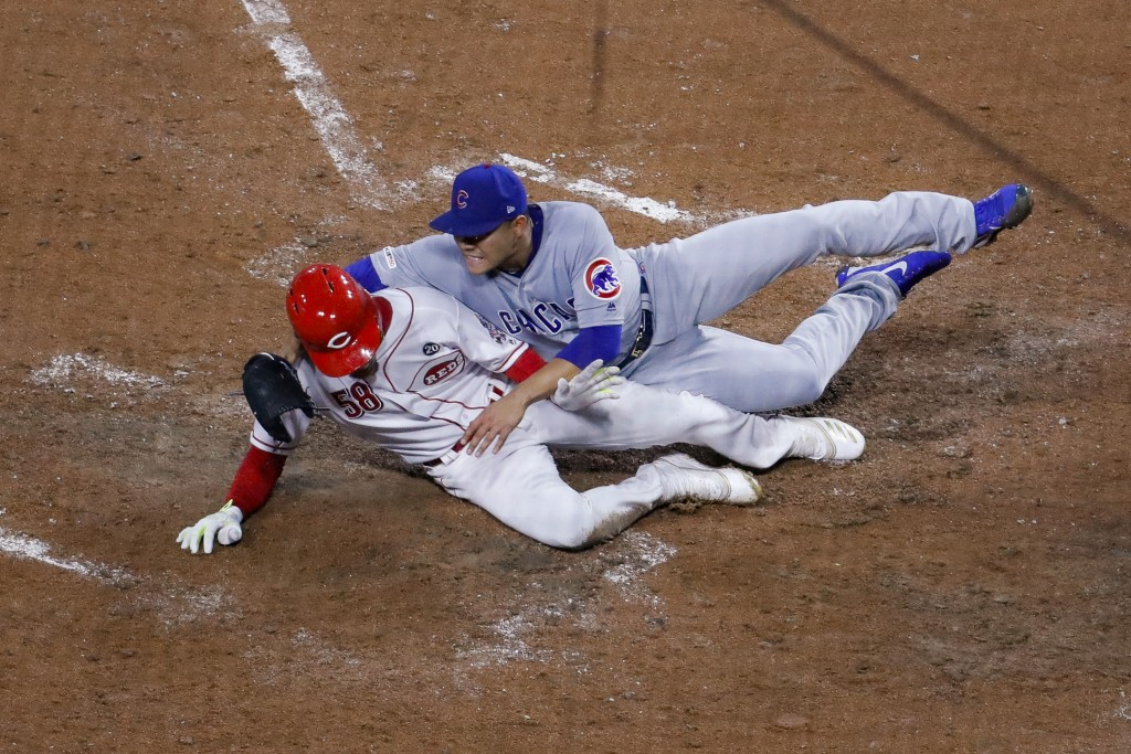 Cincinnati Reds' Luis Castillo (58) scores on a wild pitch by Chicago Cubs starting pitcher Jose Quintana, right, during the fifth inning of a basebal