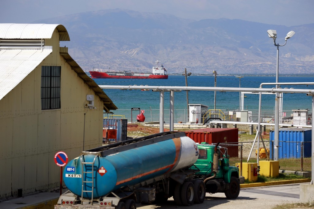 In this April 16, 2019 photo, a tanker truck waits to fill up at the Thor terminal where a ship loaded with fuel awaits to unload its cargo in Carrefo...