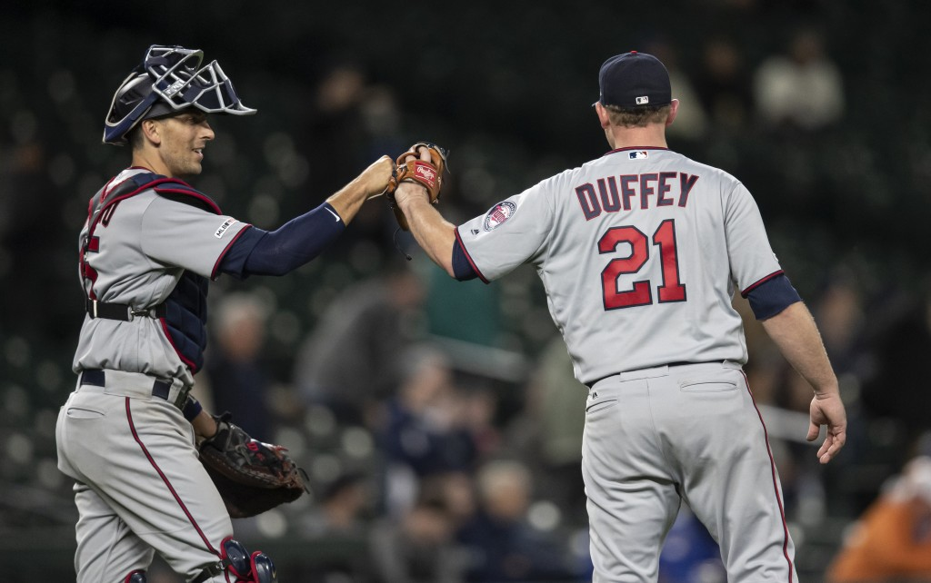 Minnesota Twins catcher Jason Castro, left, and relief pitcher Tyler Duffey celebrate after the team's baseball game against the Seattle Mariners, Thu