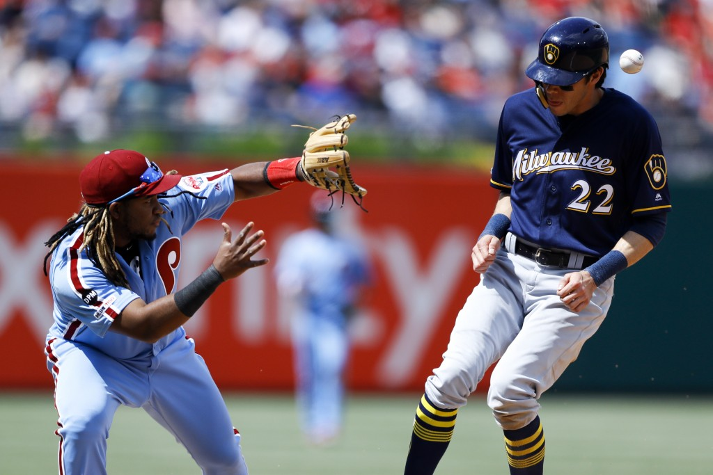 Milwaukee Brewers' Christian Yelich, right, is hit by a throw near Philadelphia Phillies third baseman Maikel Franco after Yelich advanced to third on