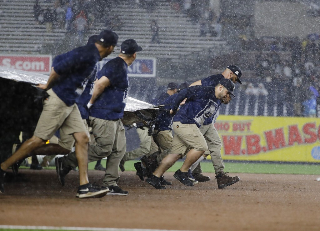 Members of the grounds crew cover the field during a rain delay in the eighth inning of a baseball game between the New York Yankees and the Tampa Bay
