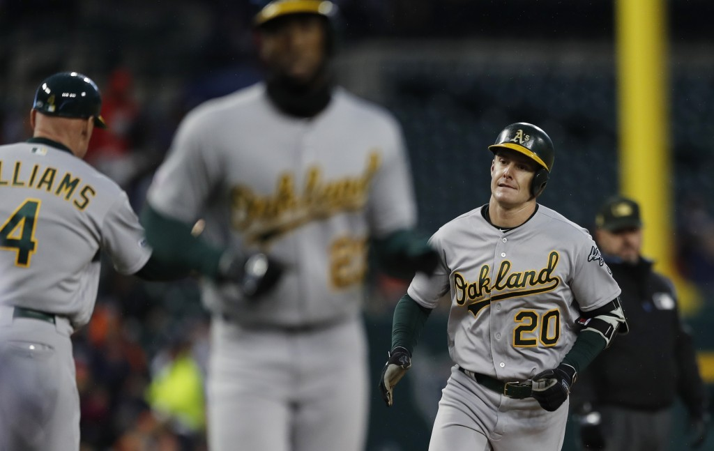 Oakland Athletics' Mark Canha (20) and Jurickson Profar, center, round third base on Canha's two-run home run during the fifth inning of a baseball ga...