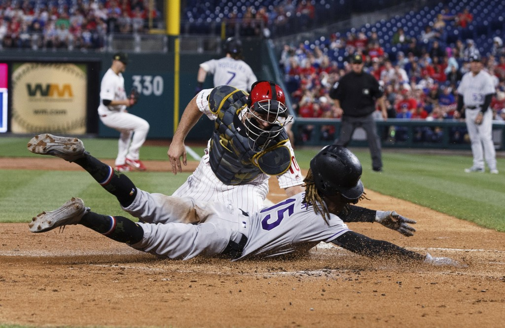 Colorado Rockies' Raimel Tapia, right, scores a run on a grounder by Brendan Rodgers (7) as Philadelphia Phillies catcher J.T. Realmuto, left, was lat
