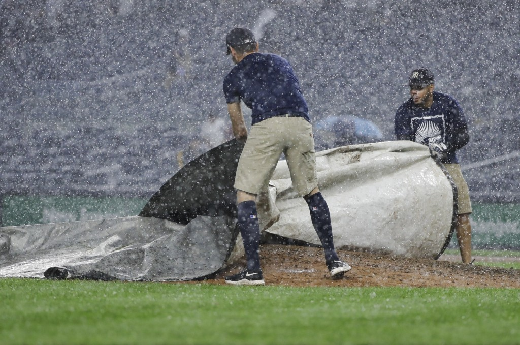 Members of the grounds crew cover the pitcher's mound during a rain delay in the eighth inning of a baseball game between the New York Yankees and the