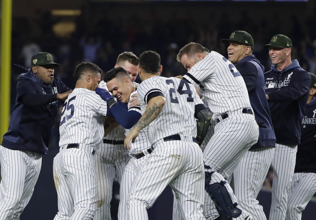 New York Yankees' Gio Urshela celebrates with teammates after hitting a game-ending RBI single during the ninth inning of the team's baseball game aga