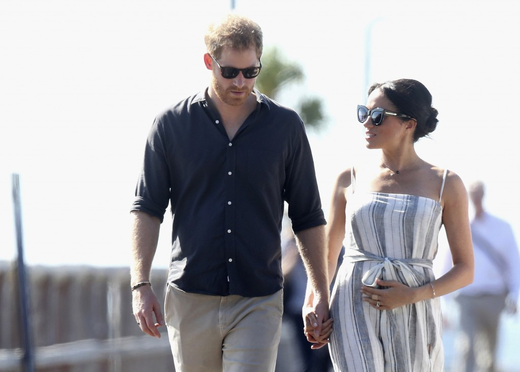 File - In this Monday, Oct. 22, 2018 file photo, Britain's Prince Harry and Meghan, Duchess of Sussex walk along the Kingfisher Bay Jetty,  in Fraser