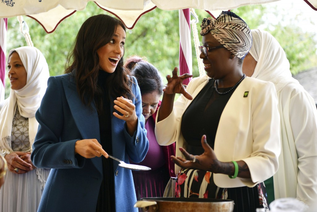 """FILE - In this Thursday, Sept. 20, 2018 file photo, Meghan, the Duchess of Sussex, left, reacts with one of the women behind the cookbook """"Together"""" d"""