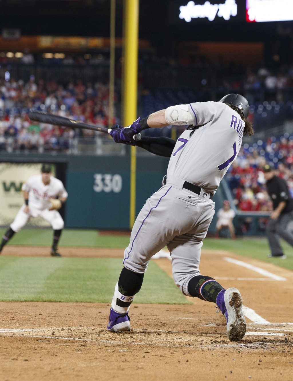 Colorado Rockies' Brendan Rodgers hits a ground ball that drove in a run during the second inning of the team's baseball game against the Philadelphia