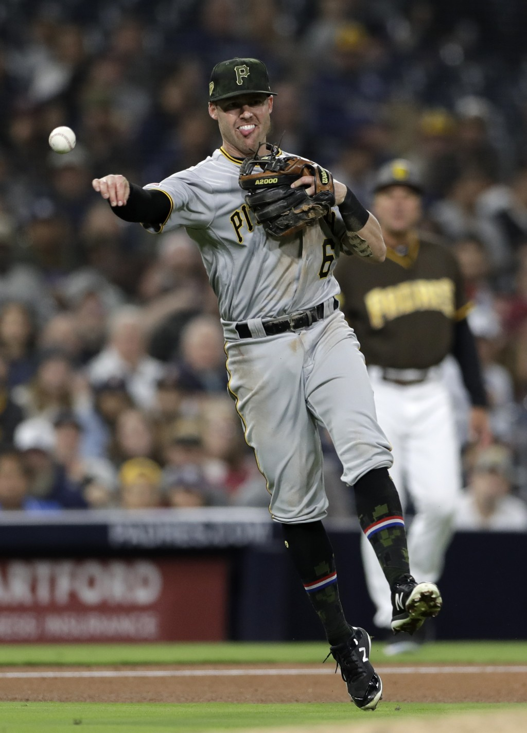 Pittsburgh Pirates third baseman Jake Elmore throws to first too late as San Diego Padres' Ty France arrives safely for a single during the fourth inn