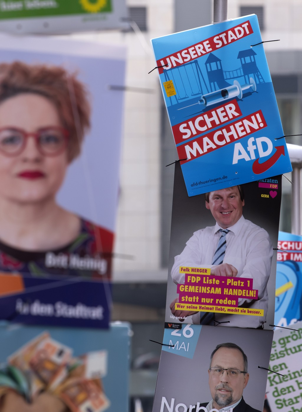 In this Friday, May 17, 2019 photo an AfD poster (top right) hangs on a street light during the street Europe and communal election campaigning of the