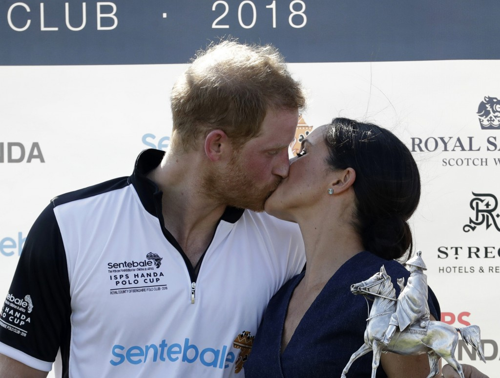 FILE - In this Thursday, July 26, 2018 file photo, Meghan, Duchess of Sussex and Britain's Prince Harry kiss during the presentation ceremony for the