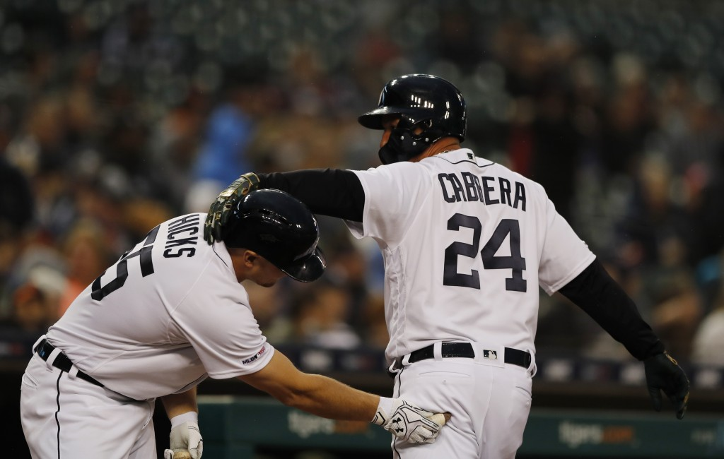 Detroit Tigers' Miguel Cabrera (24) is greeted by John Hicks after scoring during the fifth inning of a baseball game against the Oakland Athletics, F...