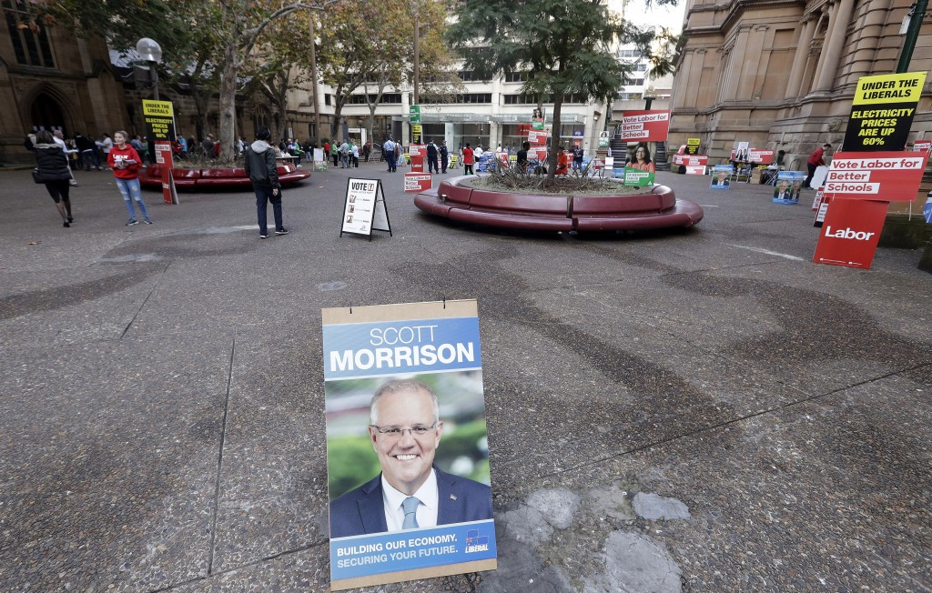 A placard with the face of Australian Prime Minister Scott Morrison is placed near the entrance of Town Hall as voters line up to cast their ballots i