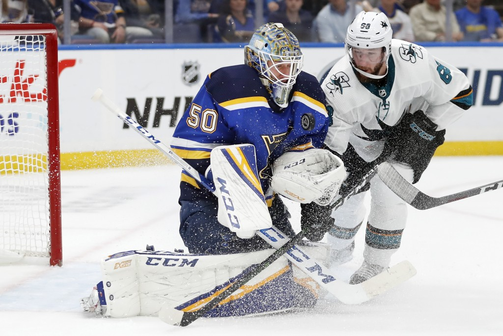 St. Louis Blues goaltender Jordan Binnington (50) protects the puck as San Jose Sharks center Melker Karlsson (68), of Sweden, closes in during the se