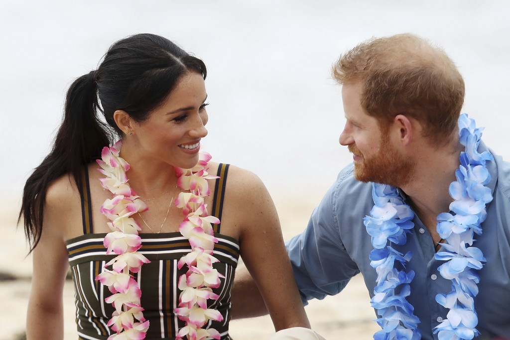 FILE - In this Friday, Oct. 19, 2018 file photo, Britain's Prince Harry and Meghan, Duchess of Sussex meet with a local surfing community group, known