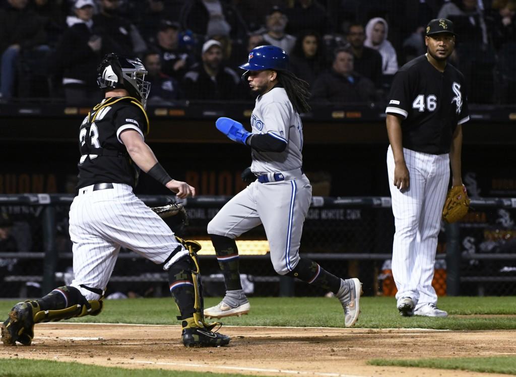 Toronto Blue Jays' Freddy Galvis, center, scores past Chicago White Sox catcher James McCann (33) and starting pitcher Ivan Nova (46) during the third