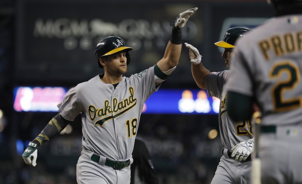 Oakland Athletics' Chad Pinder (18) is greeted at home plate after his two-run home run during the sixth inning of a baseball game against the Detroit...