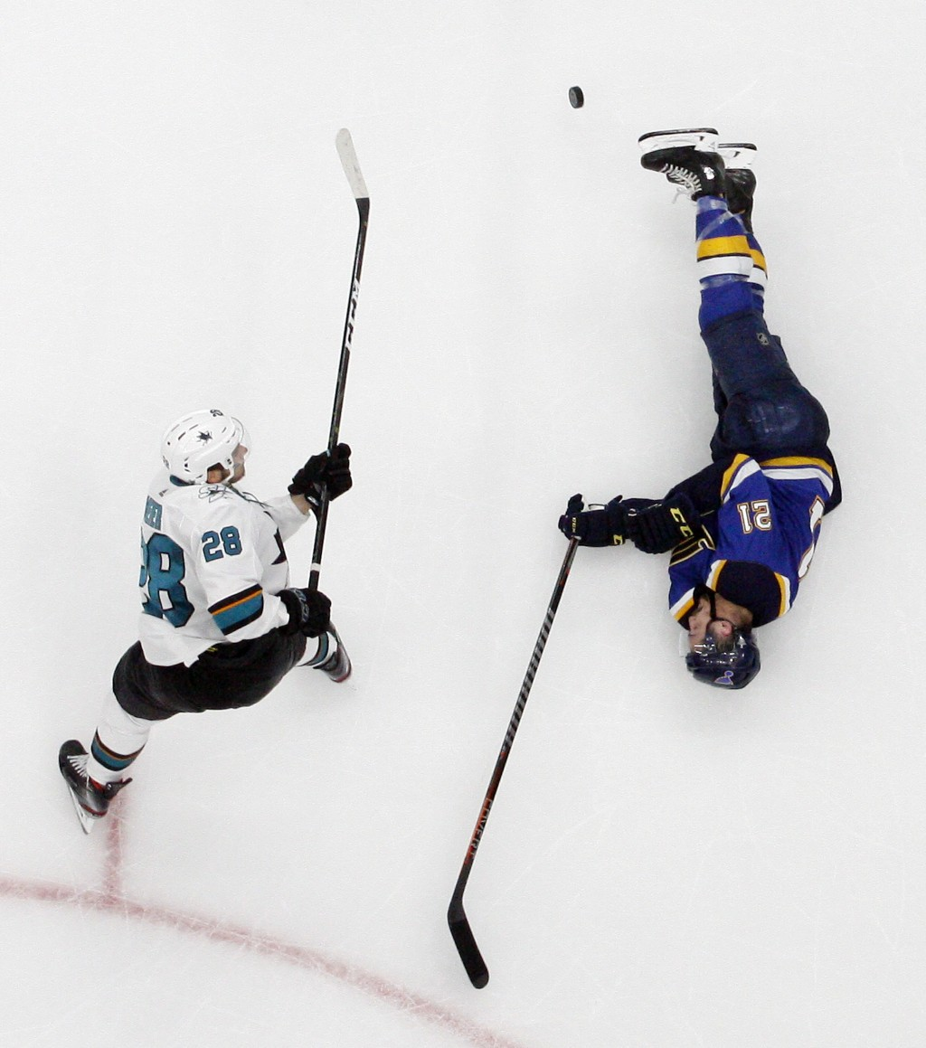 St. Louis Blues center Tyler Bozak (21) slides on the ice to block a shot by San Jose Sharks right wing Timo Meier (28), of Switzerland, during the th