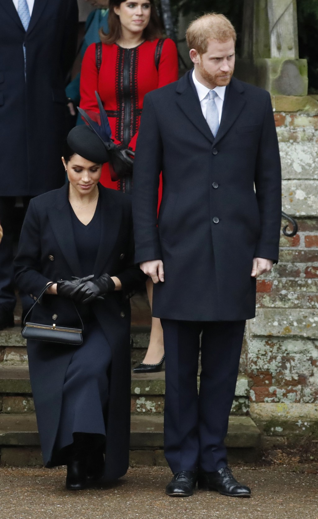 FILE - In this Tuesday, Dec. 25, 2018 file photo, Britain's Prince Harry, stands as Meghan, Duchess of Sussex curtsies to Britain's Queen Elizabeth II