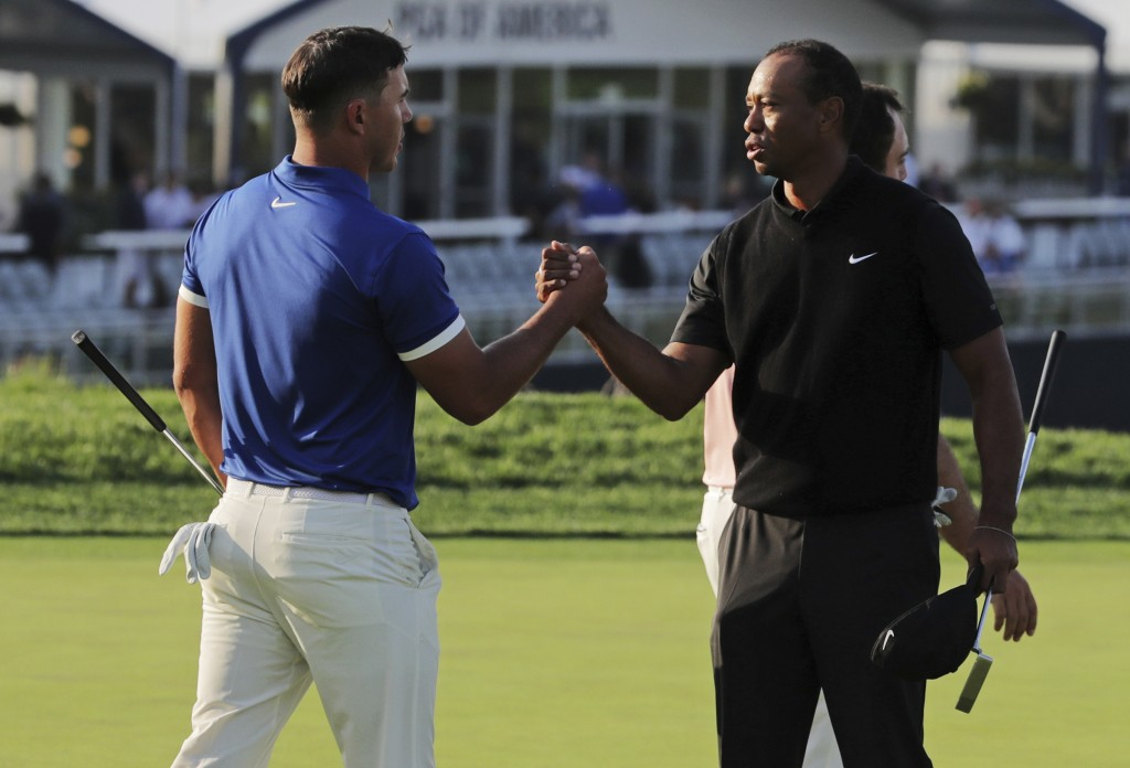 Brooks Koepka, left, shakes hands with Tiger Woods after finishing the second round of the PGA Championship golf tournament, Friday, May 17, 2019, at