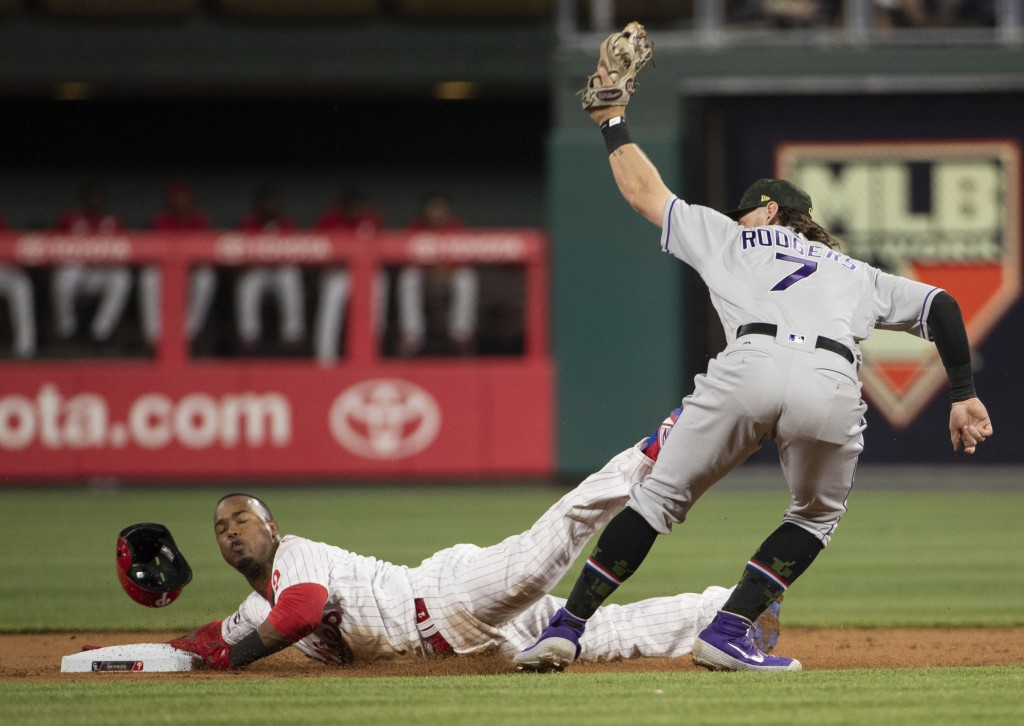 Philadelphia Phillies' Jean Segura, left, gets caught stealing with the tag by Colorado Rockies second baseman Brendan Rodgers, right, during the firs