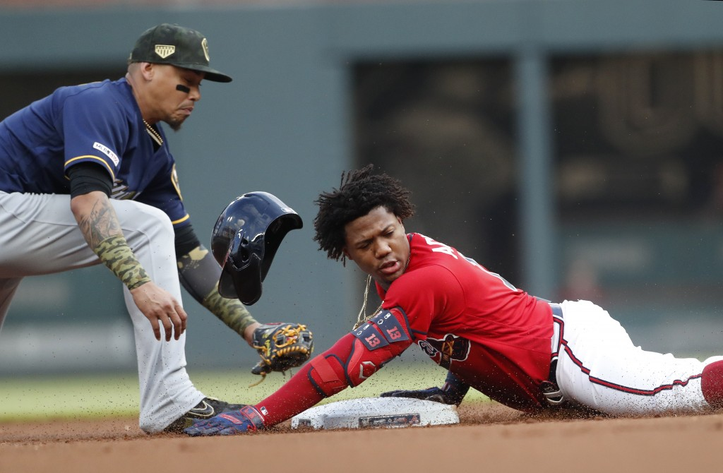 Atlanta Braves left fielder Ronald Acuna Jr. (13) is safe at second base with a double as Milwaukee Brewers shortstop Orlando Arcia (3) handles the la