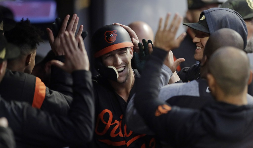 Baltimore Orioles' Stevie Wilkerson is congratulated by teammates after hitting a solo home run in the fourth inning of a baseball game against the Cl
